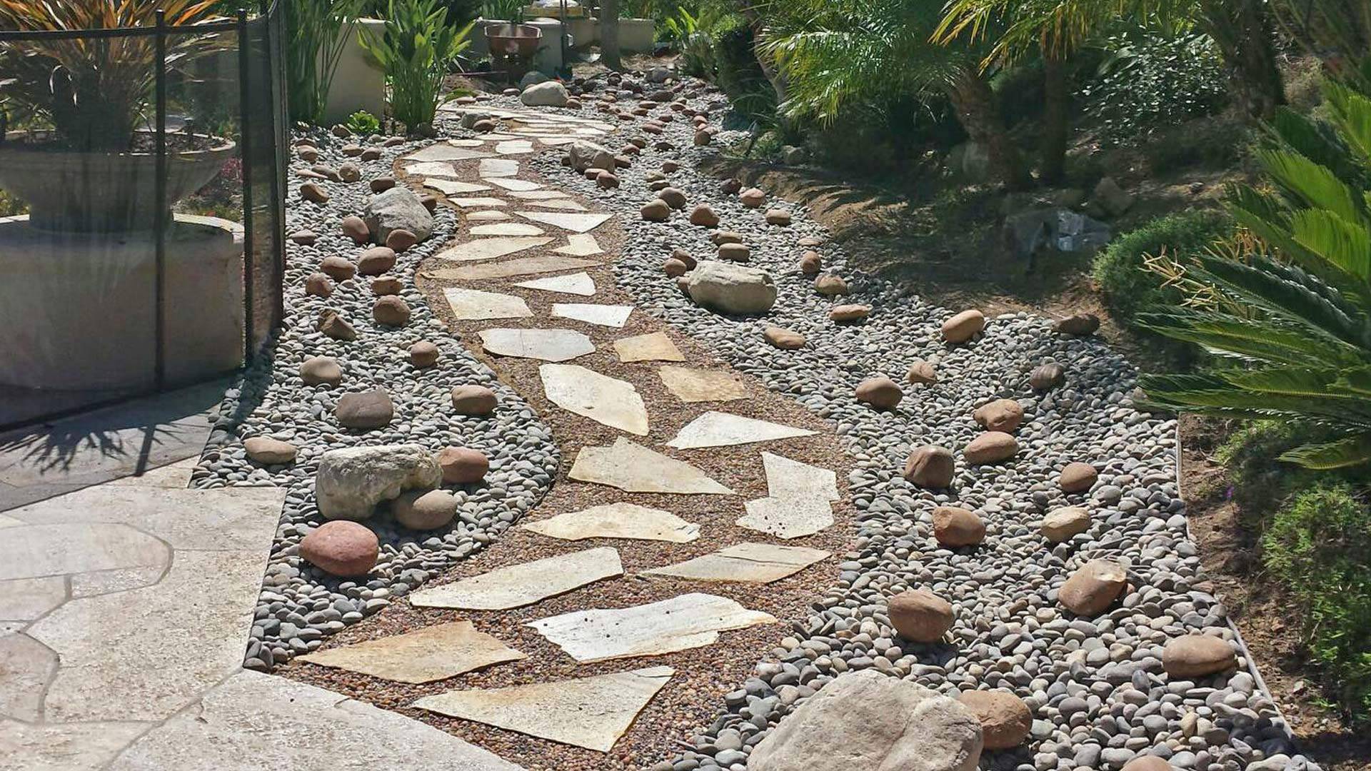A new flagstone and river rock walkway in the backyard of a home in Carlsbad.
