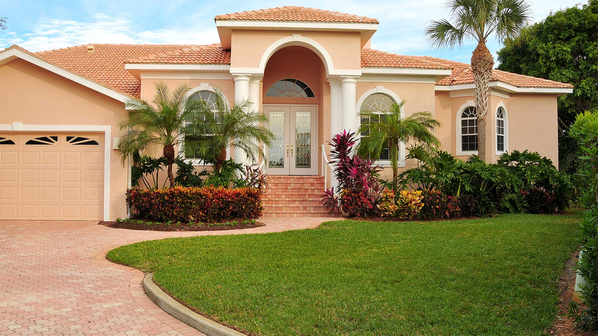 Mature landscaping and palm trees at a home that contracts us for our full-service lawn and landscape maintenance services.