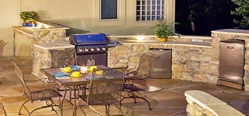 Custom outdoor kitchen with built in grill, sink, trash, and fire pit at a home in Carlsbad.